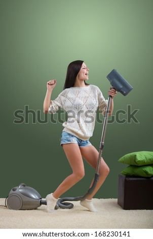 Girl sings while she tidies up the room - stock photo