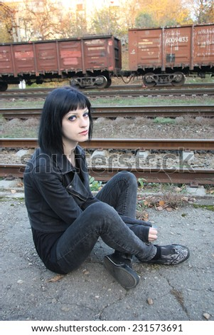 Girl sit between rails and abandon railroad station
