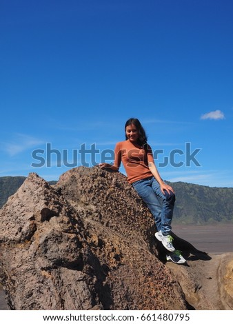 girl sit on big rock with blue sky
