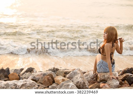 Girl sit on stone at the beach