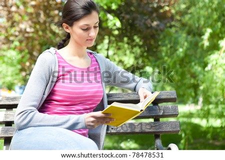 girl siting on bench  in park and reading book - stock photo