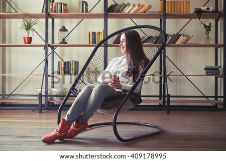 Girl sits in a chair with a cup and looking to the side - stock photo