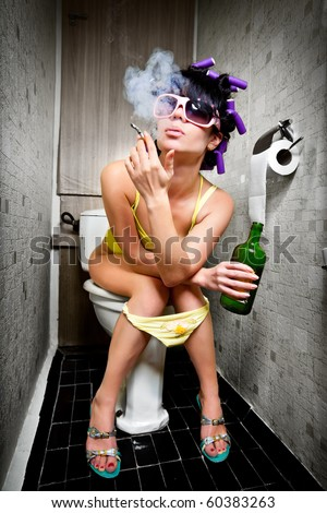 girl sits in a toilet with an alcohol bottle