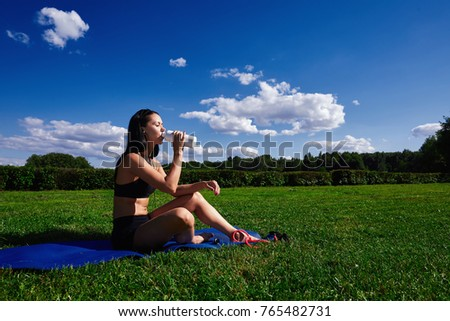Girl sits in Park on the grass on a Sunny day and drinking water.