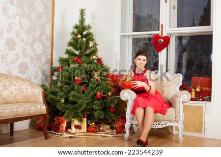girl sits near New-Year's tree - stock photo