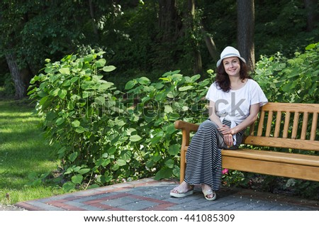 Girl sits on a bench in a city park.