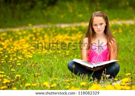 Girl sits on a grass and reads the book - stock photo