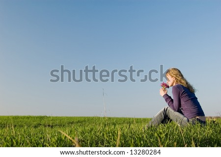Girl sits on a grass and smells a bunch of flowers - stock photo