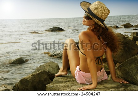 girl sits on a stone on a sea beach - stock photo