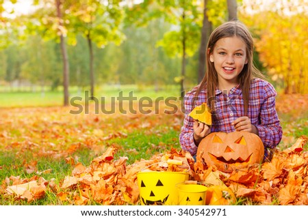 Girl sits with pumpkin in the autumn forest