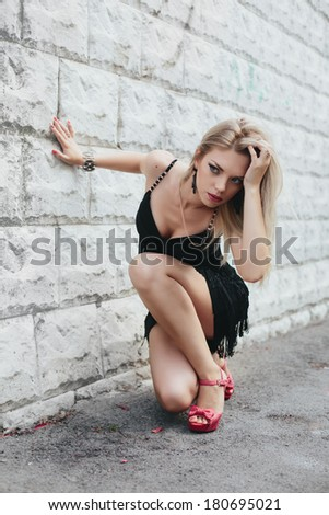 Girl sitting against the wall - stock photo