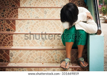 girl sitting alone at staircase in the park - stock photo