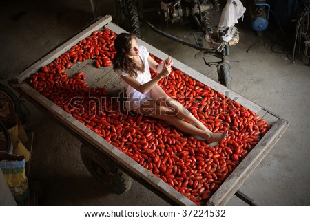 girl sitting among tomatoes - stock photo