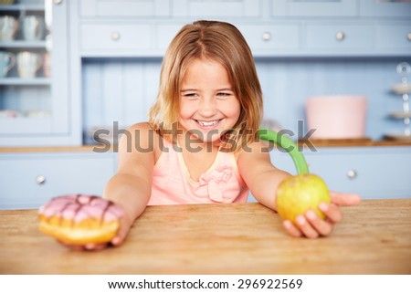 Girl Sitting At Table Choosing Cakes Or Apple For Snack - stock photo