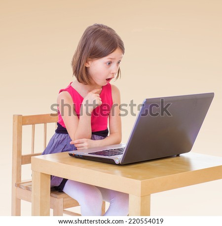 Girl sitting at the computer.The concept of development of the child, the child's upbringing. - stock photo