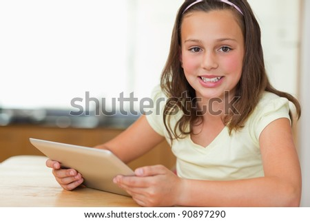 Girl sitting at the kitchen table with tablet - stock photo