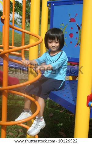 Girl sitting at the playground in the park - stock photo