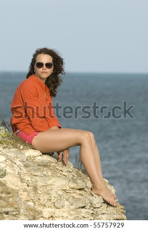 Girl sitting at the rock - stock photo