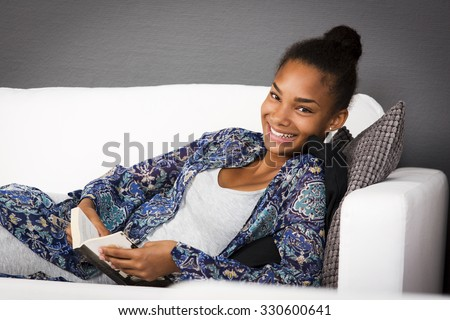 Girl sitting back in a couch with a book in her hands. She is looking into the camera with a happy smile. - stock photo