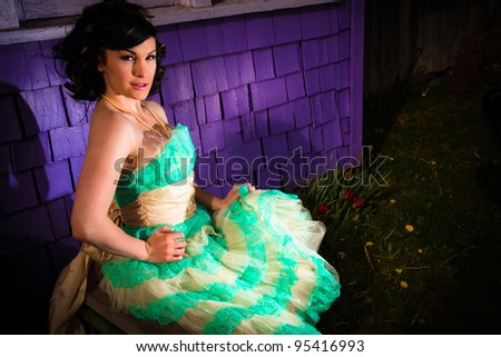 Girl sitting by a purple wall with a flashy dress on - stock photo