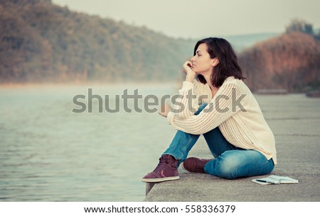 Girl sitting by lake and looking into water. Thinking.
