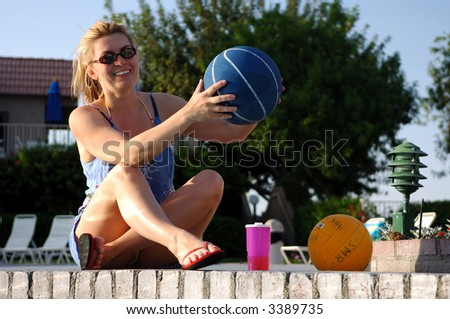 Girl Sitting By Swimming Pool Holding Basketball - stock photo
