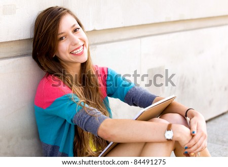 Girl sitting by the wall - stock photo