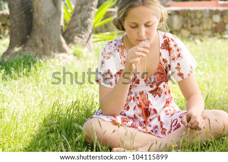 Girl sitting down on green grass, smelling a daisy flower. - stock photo