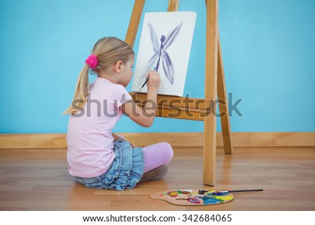 Girl sitting down painting a picture on an easel - stock photo