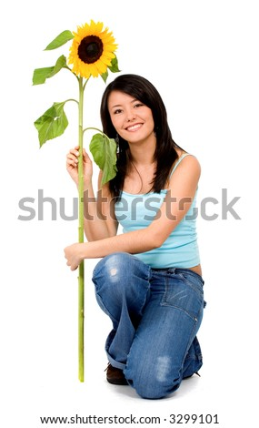 girl sitting down smiling while holding a sunflower isolated over a white background - stock photo