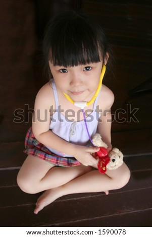 girl sitting down & testing stethoscope on toy dog - stock photo