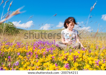 Girl sitting in a field of wild flowers - stock photo