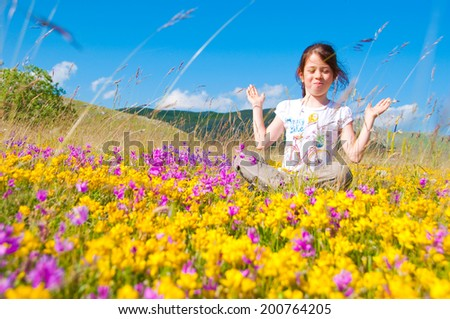 Girl sitting in a field of yellow wild flowers - stock photo