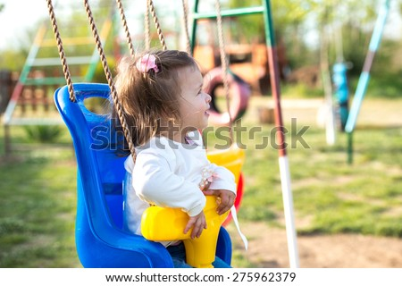 girl sitting in a park swing - stock photo