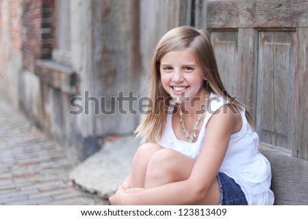 Girl sitting in alley - stock photo