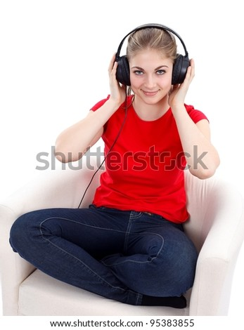 Girl sitting in an armchair listening music - stock photo