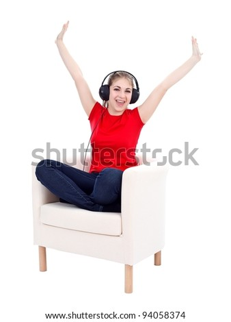 Girl sitting in armchair listening music - stock photo