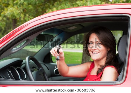 Girl sitting in car and holding keys. - stock photo