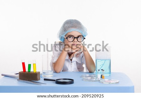 Girl sitting in chemistry class and makes the simplest experiments - stock photo