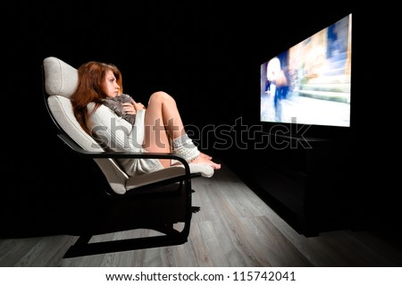 Girl sitting in front of large display in dark room with black background - stock photo