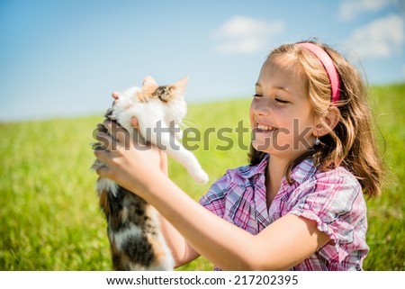Girl sitting in grass and playing with her small cat - stock photo