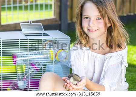 Girl sitting in the backyard with a small hamster in palms - stock photo