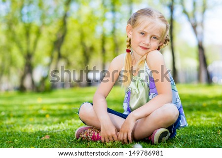 girl sitting in the grass on a summer park