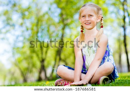 girl sitting in the grass on a summer park - stock photo