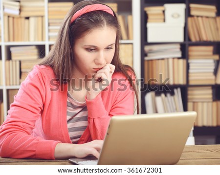 girl sitting in the library and working at a desk, using a laptop. - stock photo