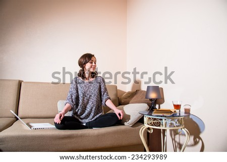 Girl sitting in the lotus position and meditates on the couch - stock photo