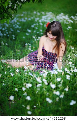 girl sitting in the spring flowery park among flowers. - stock photo