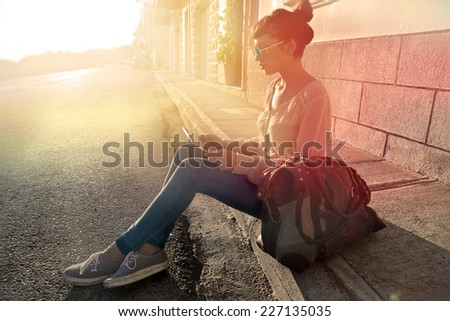 Girl sitting in the sun and using a tablet  - stock photo