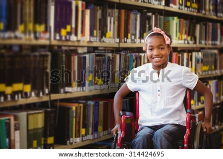 Girl sitting in wheelchair in school corridor against close up of a bookshelf - stock photo