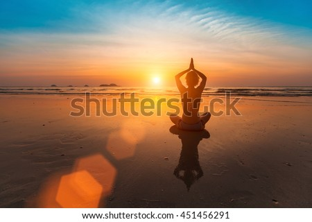 Girl sitting in yoga pose on the beach by the sea at sunset.